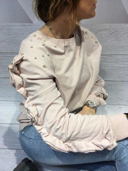 Bluza różowa z perłami i falbaną.